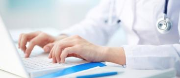 doctor's hands typing on a laptop